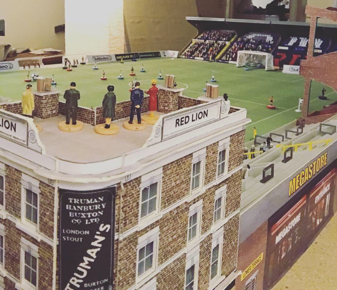 Take a look at a Subbuteo stadium with a corner pub, Oompah band and flares