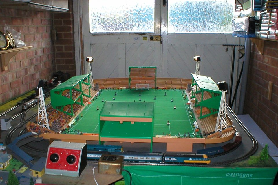 A Subbuteo stadium with a working train track